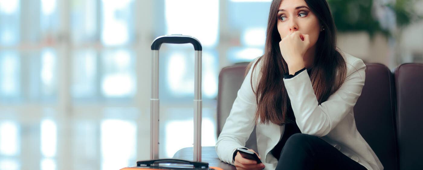 Žena sedí s kufrem v hale