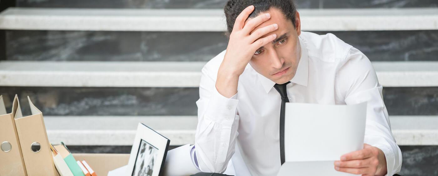 Zdrcený muž sedí na schodech s krabicí s věcmi a pročítá výpověď
