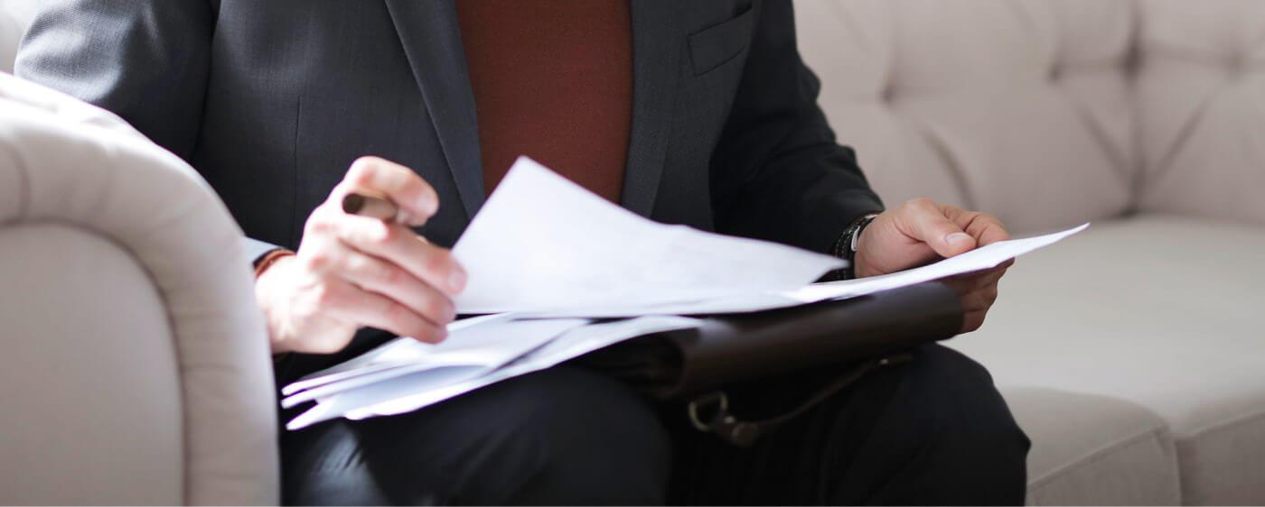 Muž na pohovce podepisující odstoupení od smlouvy